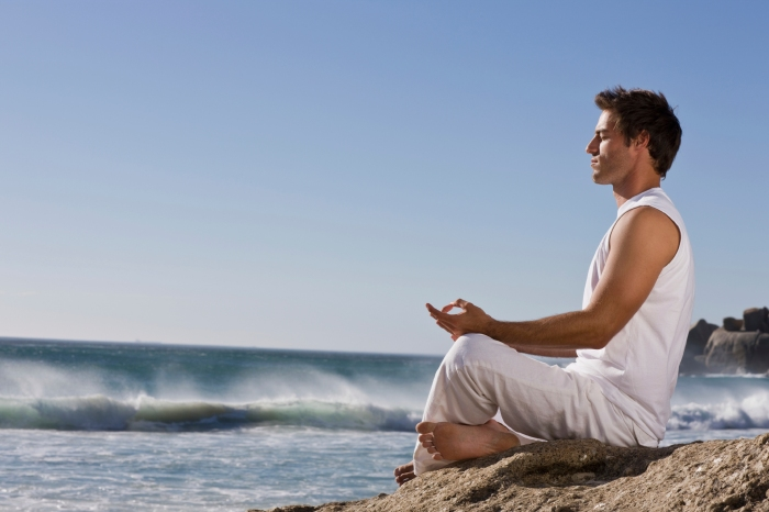 Young man meditating on rock by sea